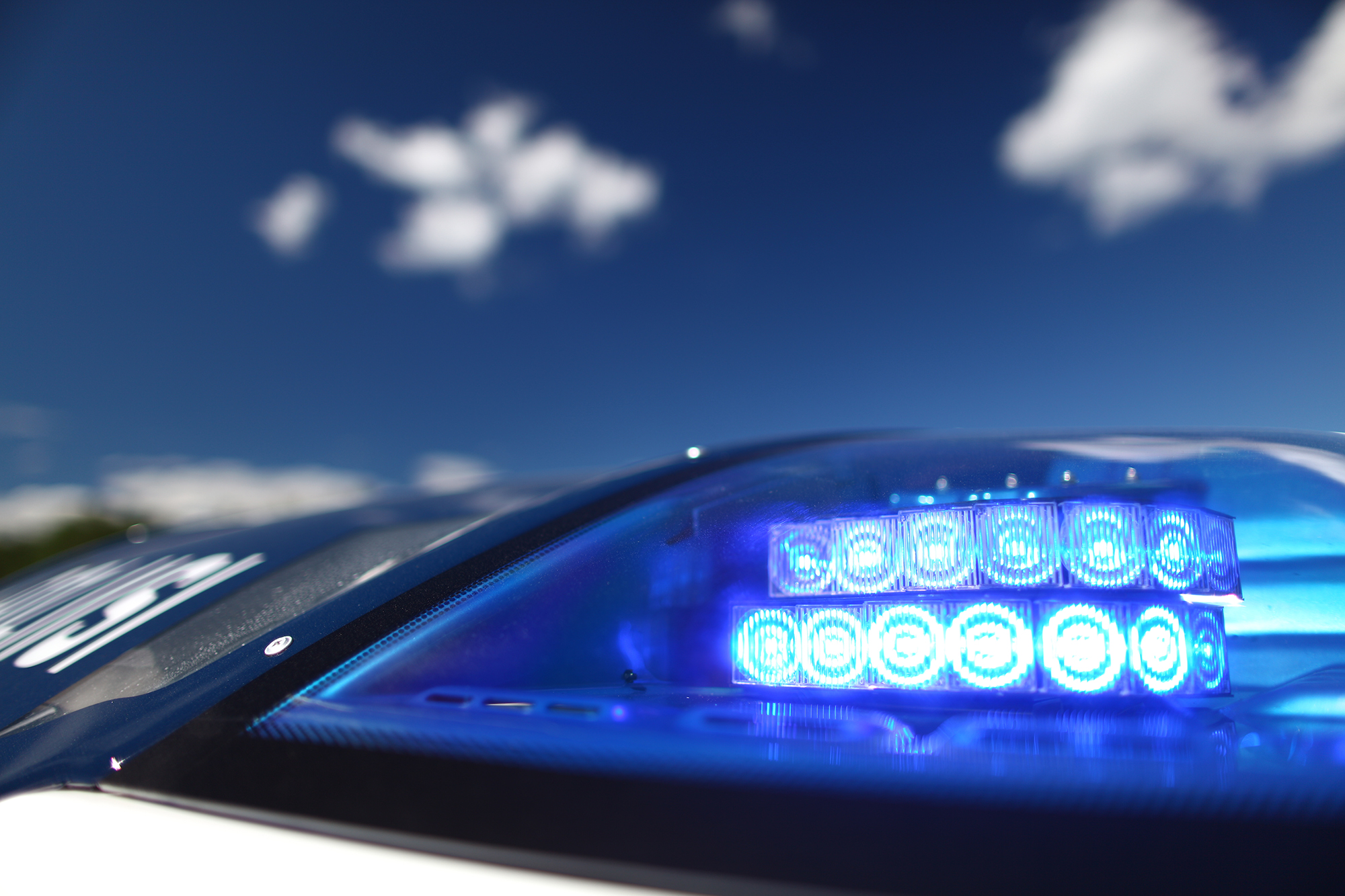 A close-up image of a police car's flashing light, with blue sky in the background.