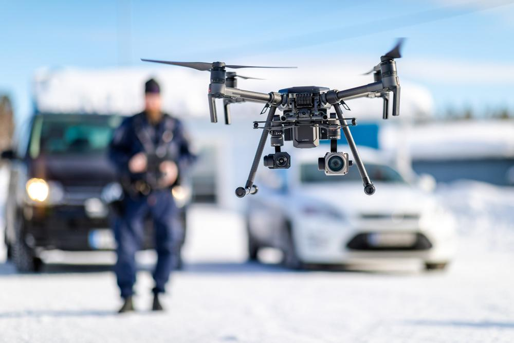 A police officer is flying a drone. Police cars are blurred in the background.